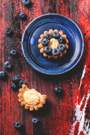 goods: Top view on blueberry mini tarts served on blue ceramic plate over black and red wooden background. Stock Photo