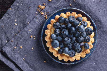 Top view on blueberry tart served on blue ceramic plate over textile napkin. Stock Photo