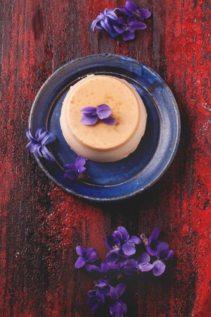 pannacotta: Top view on plate with caramel pannacotta served with violet flowers over red wooden background Stock Photo