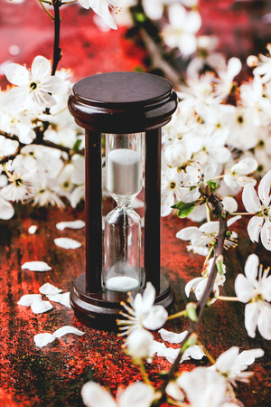 Vintage hourglass with blossom branch of cherry-tree on black and red wooden table. photo