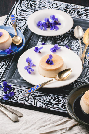 pannacotta: Plate with caramel pannacotta served with violet flowers and vintage teaspoons over black and white table