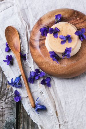 pannacotta: Top view on wooden plate with caramel pannacotta served with violet flowers over gray textile