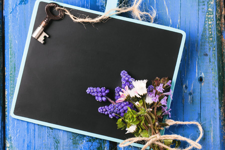Blank chalkboard with bouquet of wildflowers and vintage key over blue wooden background photo