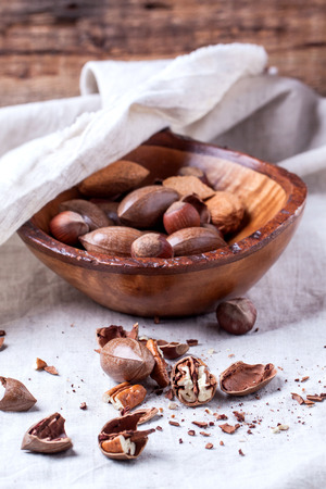 Wooden bowl with whole and chopped pecan nuts over gray textile Stock Photo