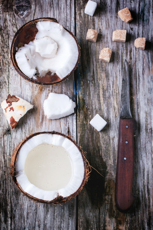 Broken coconut with coconut milk, sugar cubes and vintage knife on old wooden background. Top view