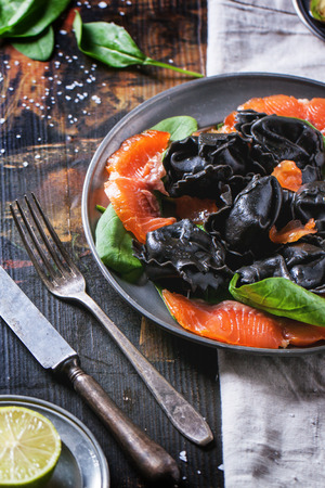 Vintage plate with black homemade ravioli with salted salmon, served on wooden table. See series photo