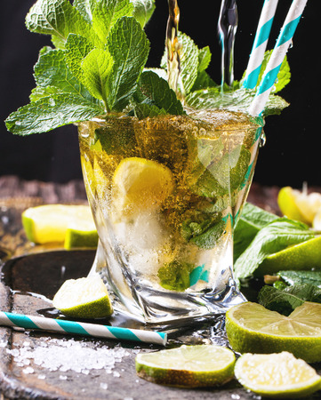 Glass of mojito cocktail with pouring rum and soda, fresh mint, limes and ice cubes over black background. photo