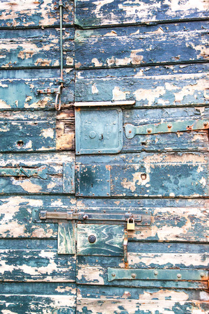 Fragment of old wooden door with locks as background photo