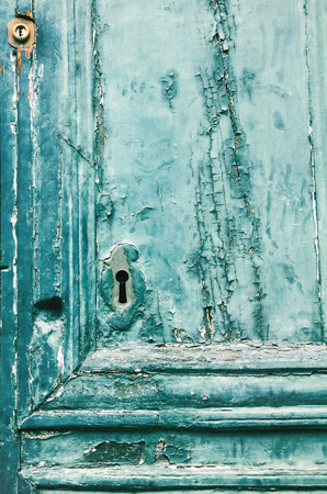 Fragment of old wooden door with keyhole as background photo