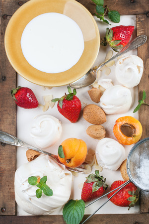 kiss biscuits: Homemade meringue with apricots, strawberries, almonds and cream. Ingredients for dessert Eton mess. Top view.