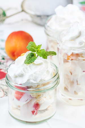 eton mess: Dessert Eton mess with merengue, berries and whipped cream, served in glass jar. Stock Photo