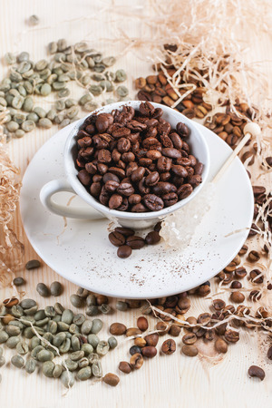 decaf: Green and brown decaf unroasted coffee beans and cup of roasted coffee beans on wooden table with chips. Stock Photo