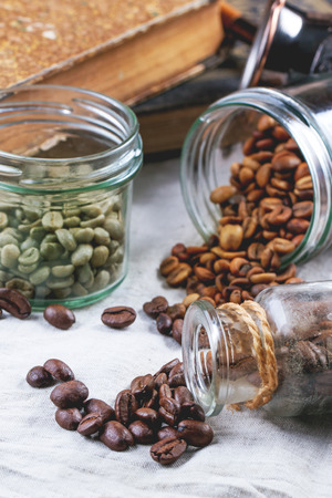 decaf: Green, brown unroasted decaf and black coffee beans in glass jars.