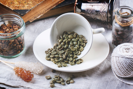 Cup of green unroasted coffee beans on table with vintage books, sugar sticks and another kinds of coffee photo