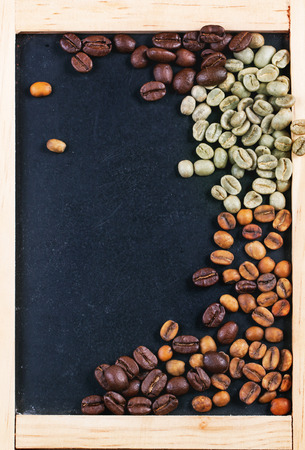 unroasted: Green, brown unroasted decaf and black coffee beans on black empty chalkboard. Top view. Stock Photo