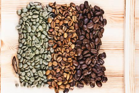 나무 위에 녹색과 갈색 디카 페인 황화과 검은 볶은 커피 콩. 스톡 콘텐츠