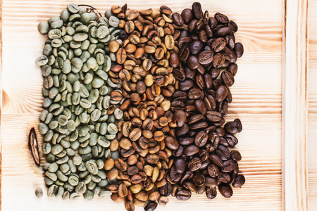 Green and brown decaf unroasted and black roasted coffee beans over wooden . Imagens