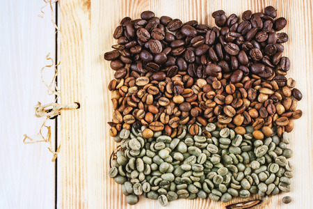 unroasted: Green and brown decaf unroasted and black roasted coffee beans over wooden . Stock Photo