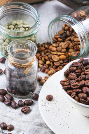decaf: Green, brown unroasted decaf and black coffee beans in glass jars and cup.