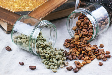 decaf: Glass jars with green and brown decaf unroasted coffee beans on table with vintage books