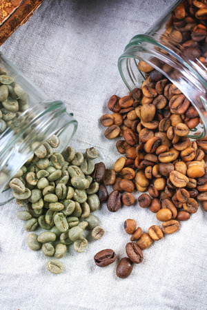 decaf: Glass jars with green and brown decaf unroasted coffee beans on tablecloth