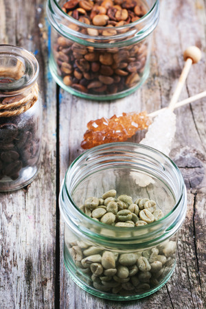 unroasted: Green, brown unroasted decaf and black coffee beans in glass jars over wooden .