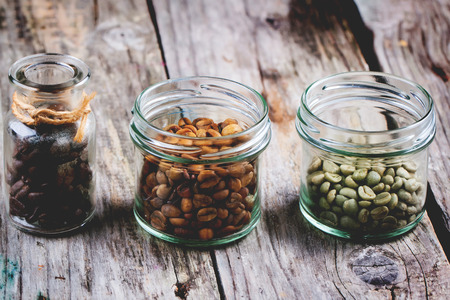 Green, brown unroasted decaf and black coffee beans in glass jars over wooden . photo
