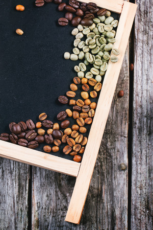 decaf: Green, brown unroasted decaf and black coffee beans on black empty chalkboard over wooden table. Top view.