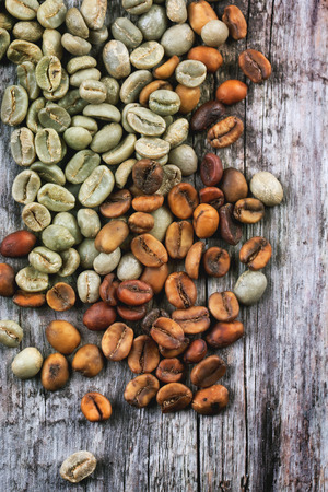 unroasted: Green and brown decaf unroasted coffee beans over wooden . Stock Photo