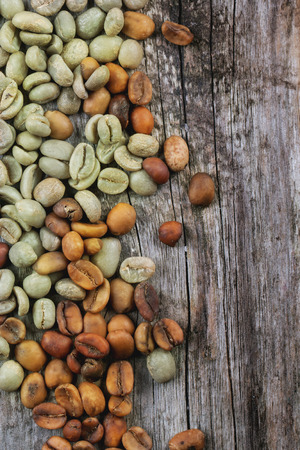 decaf: Green and brown decaf unroasted coffee beans over wooden . Stock Photo