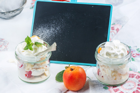 eton mess: Dessert Eton mess with merengue, berries and whipped cream, served in glass jar on table with empty chalkboard.