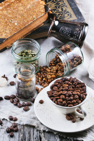 unroasted: Green, brown unroasted decaf and black coffee beans in glass jars and cup.