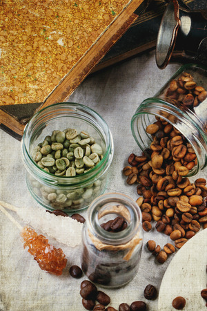 unroasted: Green, brown unroasted decaf and black coffee beans in glass jars. With retro texture