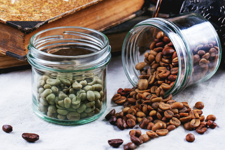 Glass jars with green and brown decaf unroasted coffee beans on tablecloth photo