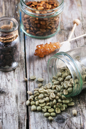unroasted: Green, brown unroasted decaf and black coffee beans in glass jars over wooden background. See series