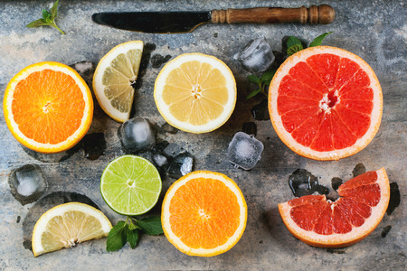 Set of sliced citrus fruits lemon, lime, orange, grapefruit with mint, ice and vintage knife over metal background. Top view. photo