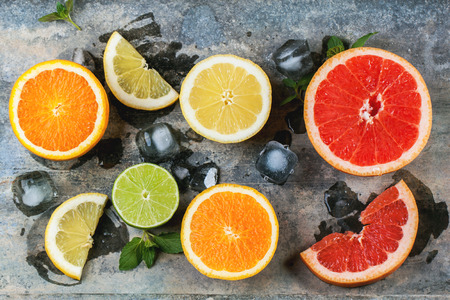 Set of sliced citrus fruits lemon, lime, orange, grapefruit with mint and ice over metal background. Top view. photo