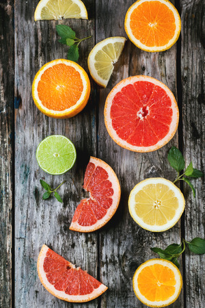 Set of sliced citrus fruits lemon, lime, orange, grapefruit with mint over wooden background. Top view. photo
