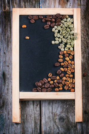 unroasted: Green, brown unroasted decaf and black coffee beans on black empty chalkboard over wooden table. Top view.