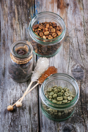 decaf: Green, brown unroasted decaf and black coffee beans in glass jars over wooden background. See series