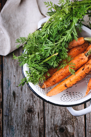 Bunch of fresh carrot with soil in white colander over wooden table. Top view. photo