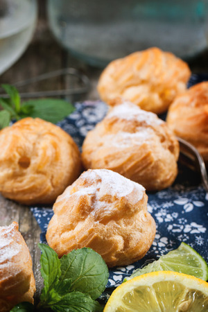 Close up of homemade cakes profiteroles served with lemon and mint Stock Photo - 29093706