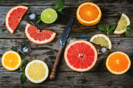 Set of sliced citrus fruits lemon, lime, orange, grapefruit with mint, ice and vintage knife over wooden background. Top view.