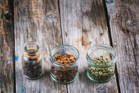 unroasted: Green, brown unroasted decaf and black coffee beans in glass jars over wooden background.