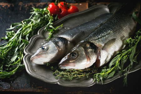 Tow raw fish seabass served with herbs and cherry tomatoes on vintage plate over black wooden table photo