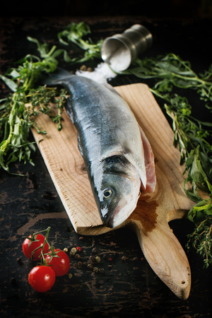 Raw fish seabass served with herbs, sea salt and cherry tomatoes on wooden cutting board over black wooden table. photo