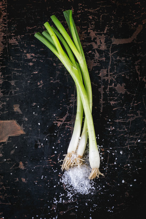 Green onions with sea salt over black wooden table. Top view photo