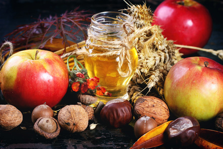 Glass jar of honey with apples, ears of wheat, chestnuts and walnuts over black wooden table photo