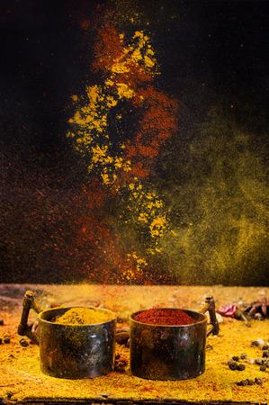 Espiral de mezcla de especias pimiento rojo y la cúrcuma de tazas de metal de época sobre fondo negro. Concepto.