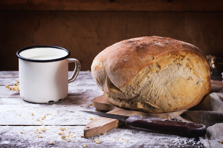 Fresh homemade bread on wooden cutting board with vintage knife and mug of milk served over wooden table with flour photo